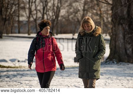 Prague, Czech Republic. 01-31-2021. Two Woman Walking And Talking On Snow Park Letna, During Cold Fr