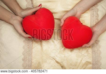 Lgbt Concept. Womens Hands Holding Red Hearts In The Bed
