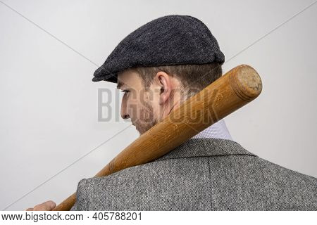 Portrait Of A 35-year-old Man In A Cap And With A Baseball Bat On A Light Background Of A Threatenin