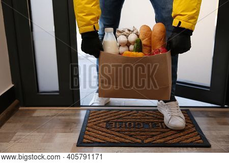 Courier Bring Paper Bag With Food To Doorway, Closeup. Delivery Service During Quarantine Due Covid-