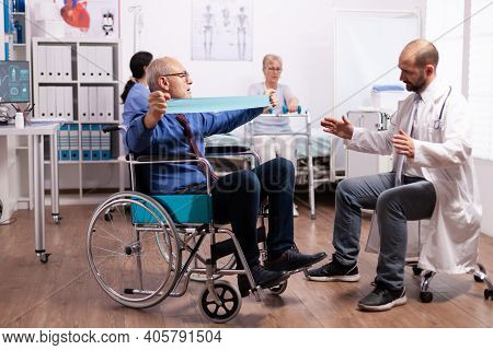 Disabled Senior Man Doing His Exercises In Hospital With Doctor. Elderly Invalid Patients In Hospita