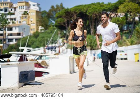 Young Couple Training Together Running Near The Boats In A Harbour