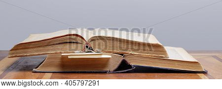 Wo Old Open Books With Bookmarks Lie On A Wooden Table