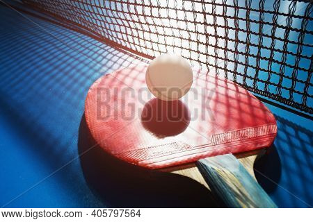 A Red Table Tennis Racket And A White Ball Lie On The Surface Of The Table Next To The Net. Sports G