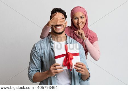 Surprise Gift. Romantic Muslim Woman Covering Her Husbands Eyes And Giving Present, Loving Islamic L