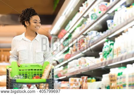 Black Woman Doing Grocery Shopping In Supermarket Looking At Full Shelves Buying Food, Standing With