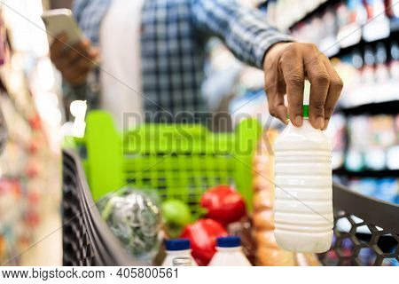 Unrecognizable Black Guy Doing Grocery Shopping Putting Products In Cart Full Of Food In Supermarket