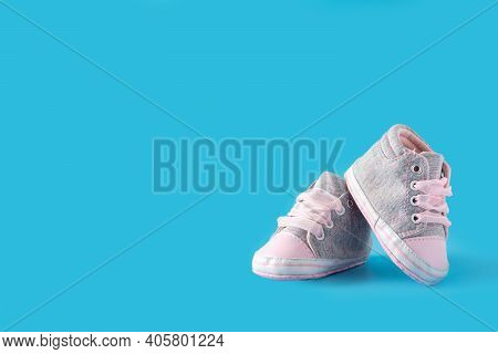 Pink And Blue Baby Shoes On Blue Background.copy Space