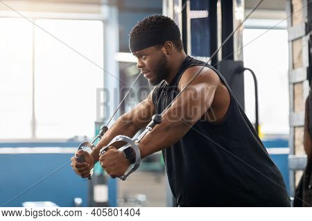 Young Black Sportsman Training Triceps On Block Exerciser In Gym, Side View, Looking At Copy Space.