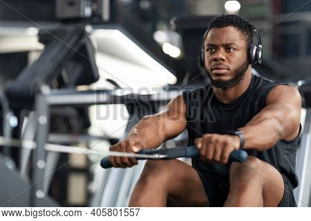 Closeup Of Handsome African American Sportsman Training Body On Modern Rowing Exerciser In Gym, Copy