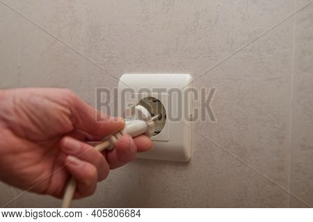 A Man's Hand Plugging In An Electrical Plug