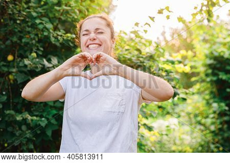 Young Woman Smiling Outdoor. Beautiful Brunete Girl Showing Heart Sign With Hands On Park Or Garden