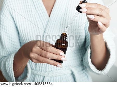 A Young Girl With Vitiligo Uses Moisturizing Serum And Drops A Drop On Her Hands. Beauty Skin Care W