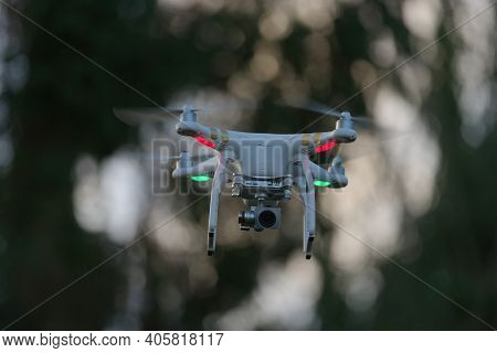 Great Malvern, United Kingdom, 27th December, 2020: Drone Quadcopter Hovering In Front Of Trees, Blu