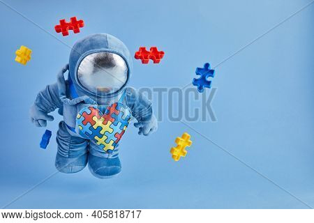World Autism Awareness Day Background. Blue Plush Astronaut Toy With Puzzle Heart, Autism Symbol, On