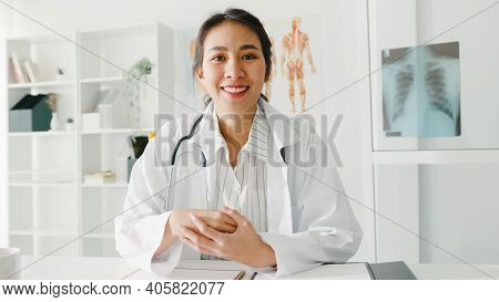 Young Asia Lady Doctor In White Medical Uniform With Stethoscope Using Computer Laptop Talk Video Co