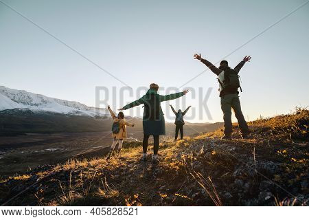 Happy Hikers Stands With Raised Arms And Looking At Sunset Mountains