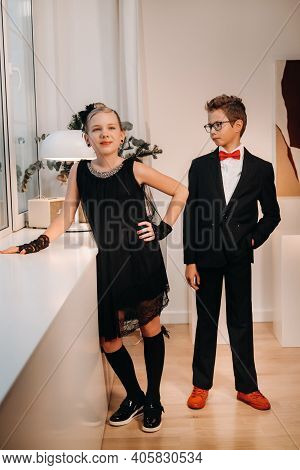 Stylish And Elegant Boy And Girl Stand At The Window In The Interior Of The House