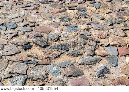 The Texture Of An Ancient Road With Paving Stones. Natural Stone Texture Close-up Of An Ancient Pave