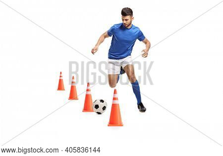 Full length portrait of a soccer player training with obstacle cones isolated on white background
