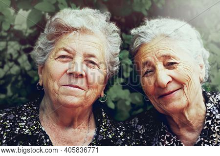 Two old happy ladies outdoors portrait. Elderly joyful sisters smiling and looking at camera