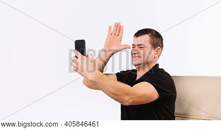 Smiling Man Sitting In A Chair Communicates By Video Using Gestures And Shows A Sign Means Dad. Whit