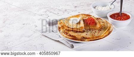 Traditional Russian Crepes Blini Stacked In A Plate With Red Caviar, Fresh Sour Cream On Light Backg