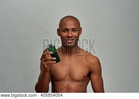 Waist-up Photo Of A Person With Abs Having A Glass Bottle Of Cosmetic Liquid