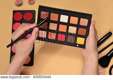 Eye Shadow Palette On Woman Hand. Professional Makeup Products With Cosmetic Beauty Products, Founda
