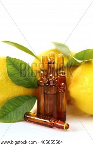 Vitamin C Injection.a Solution Of Vitamin C In Brown Glass Ampoules Set, Lemons On A White Backgroun