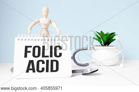 The Text Folic Acid Is Written On Notepad And Wood Man Toy Near A Stethoscope On A Blue Background.