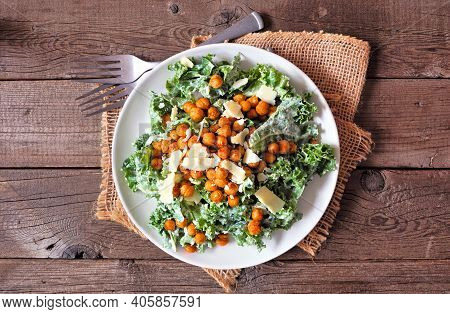 Vegetarian Caesar Salad With Chickpeas, Kale And A Yogurt Dressing. Overhead View Table Scene On A R