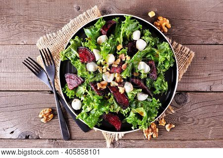 Healthy Kale And Beet Salad With Cheese And Walnuts. Above View Table Scene Over A Rustic Wood Backg