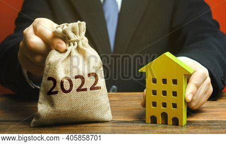 Money Bag 2022 And A Wooden House In The Hands Of A Businessman. Real Estate Concept. Family Budget