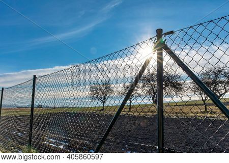 Green Wire Fence. Private Property. Fence Around The Garden. Sunrise Behind The Fence.