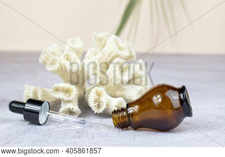 Bottle For Essential Oils And Cosmetics. Brown Cosmetic Bottle, Pipette And Corral On A Beige Backgr