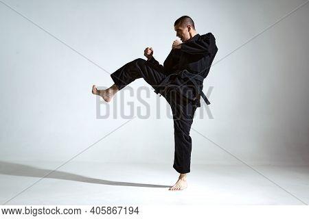 Fighting Guy In Black Kimono Fighter Shows Jiu Jitsu Technique On Studio Background With Blank Space