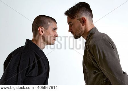 Guys In Kimono Standing In Stance Face To Face Before Karate Fight Workout On White Studio Backdrop,