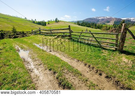 Rural Landscape In Mountains. Wooden Fence Along The Path Through Grassy Fields On Rolling Hills. Sn