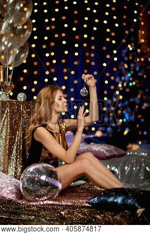 Beautiful Curly Blonde Woman In A Gold Sequins Party Dress Is Holding Mirror Ball In Luxury Interior
