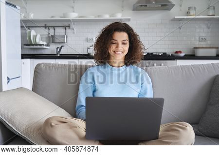 Happy Hispanic Teen Girl Holding Laptop Computer Device Technology Sitting On Couch At Home. Smiling
