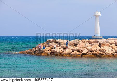 Ayia Napa, Cyprus - June 12, 2018: Fishermen Are On Breakwater Near White Lighthouse Tower, Agia Nap