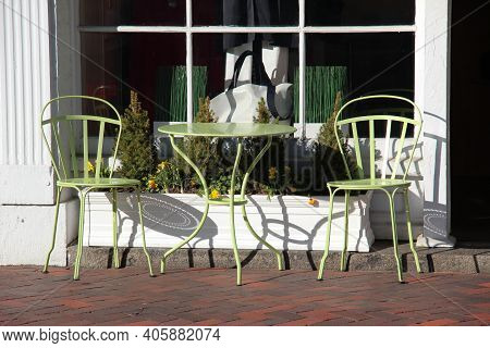 Pastel Green Bistro Table And Chairs On A Sunny Day In Front Of A Glass Window