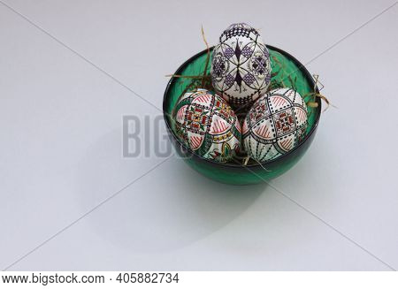 Isolated Traditional Handmade Easter Eggs In Glass Bowl On Hay. Hand Wax Painting Technique From Buc