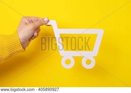The Shopping Cart In Female Hand Over Yellow Background