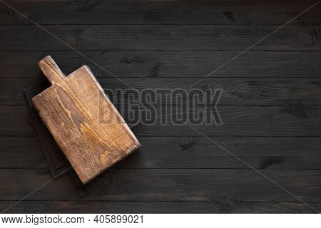 Empty Wooden Board On Black Wooden Kitchen Table, Top View, Copy Space. Wooden Platter, Copy Space.
