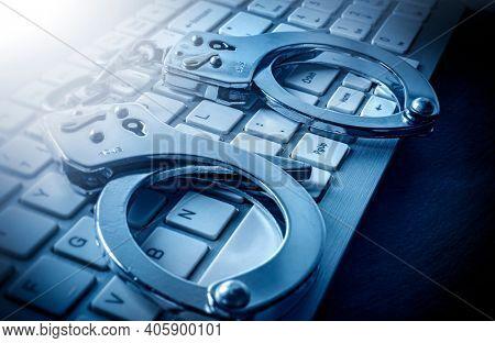Computer keyboard and handcuffs, close up