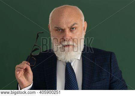 Professor Or Serious Teacher. Elderly Man Teacher On A Blank Chalkboard During Lesson, Teaching Clas