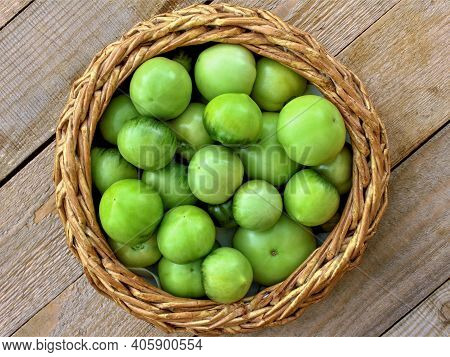 Green Tomato (unripe) In Wicker Basket On Wooden Background. Unripe Green Tomato In Bowl For Fried D