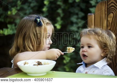 Sister Feeding Brother. Girl Feeds Baby Boy With A Spoon. Kid Food.